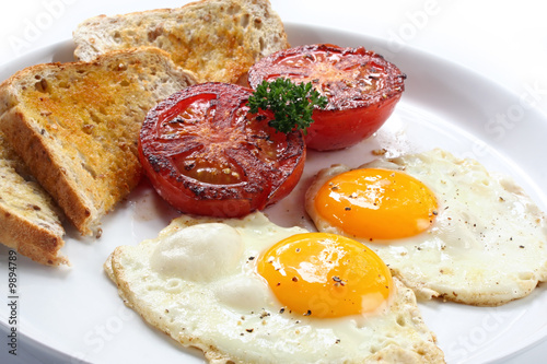 Foto op Plexiglas Gebakken Eieren Breakfast of fried eggs and tomatoes, with wholewheat toast.
