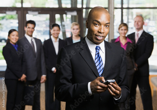 African businessman using cell phone in front of co-workers Plakát