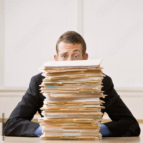 Fotografie, Obraz  Frustrated businessman looking at pile of file folders