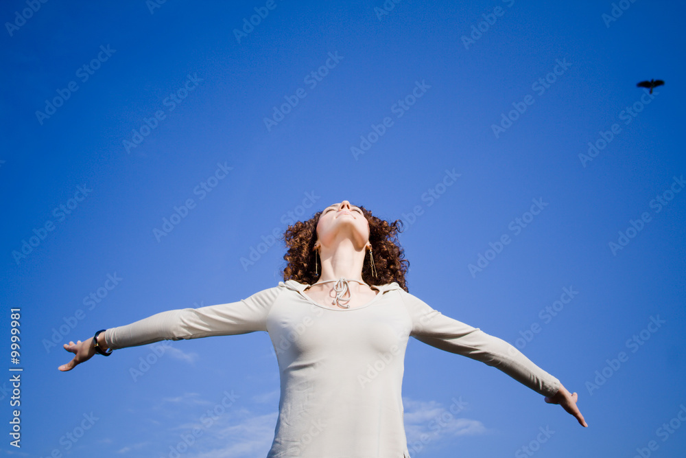 Fototapeta Young woman agains blue sky with arms outstreched