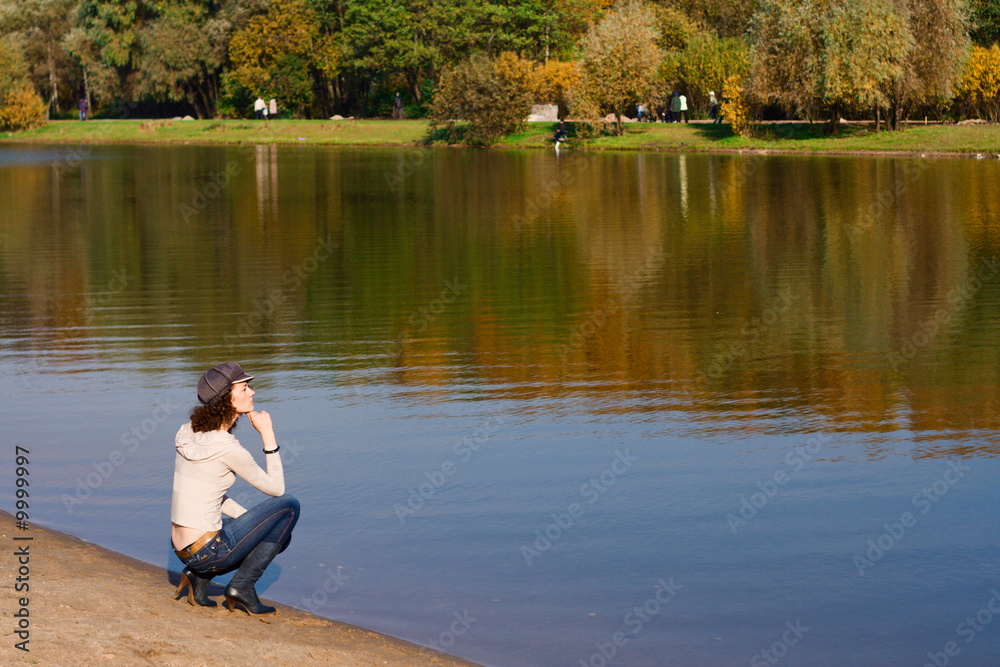 Fototapeta Young pretty woman sitting on the border of a river