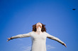 Leinwandbild Motiv Young woman agains blue sky with arms outstreched