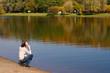 Leinwandbild Motiv Young pretty woman sitting on the border of a river