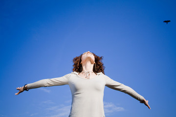 Young woman agains blue sky with arms outstreched