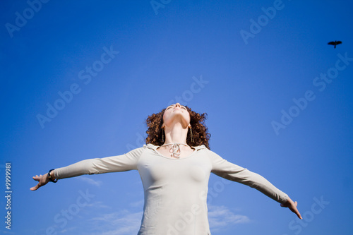 Obraz Young woman agains blue sky with arms outstreched - fototapety do salonu