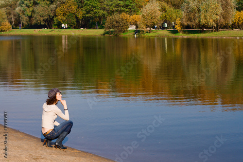 Fotografia, Obraz Young pretty woman sitting on the border of a river