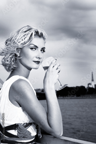 Photo  Beautiful blond girl drinks champagne near the river