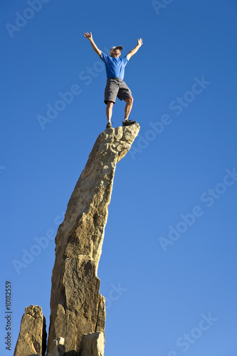 Fotografie, Obraz  Man on the summit of a rock spire.
