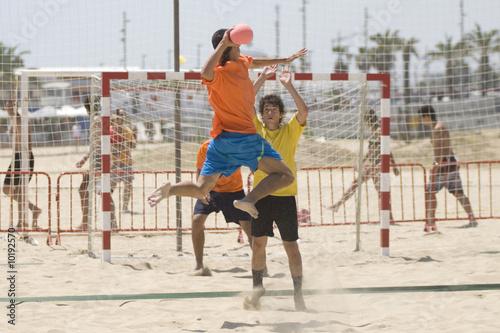 Handball player jumping with the ball on a handball beach matc
