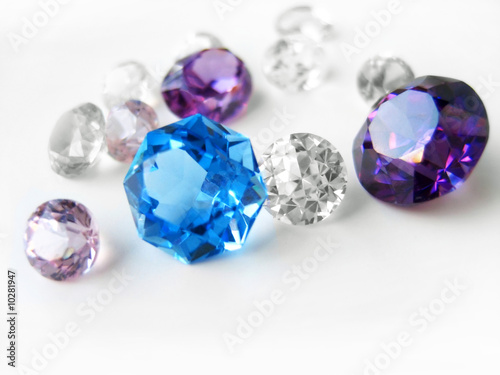 Blue & purple & colorless gems on white background