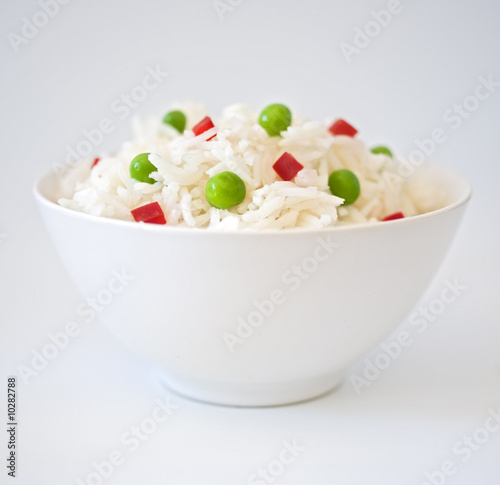 Photo  bowl of rice with peas an peppres on white