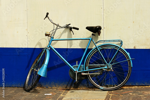 Fotobehang Fiets Abandoned bike in front of a painted wall