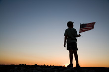 Young Boy Holding An American Flag At Sunset.