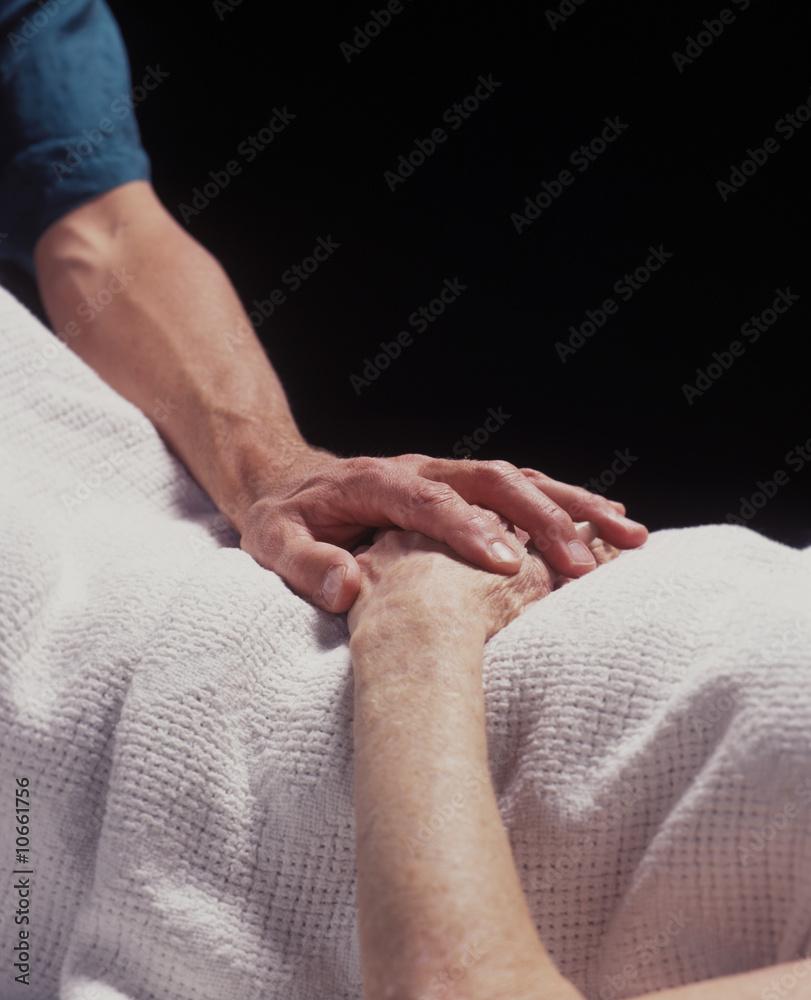 Fototapeta hand of a healer touches the hand of the elderly infirmed