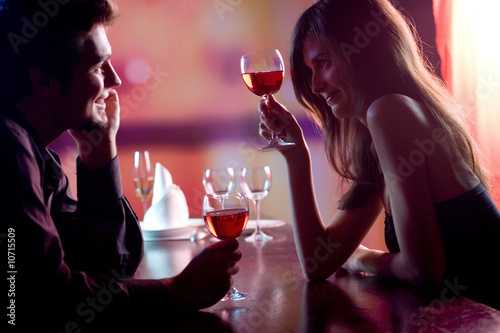 Fotobehang Restaurant Young couple sharing a glass of red wine in restaurant