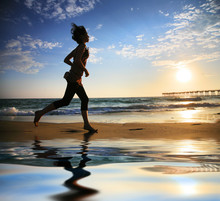 Woman Running By The Ocean At Sunset