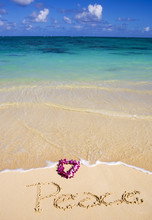 On A Beach In Hawaii, The Word Peace Is Written In The Sand