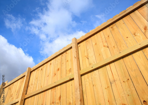 Wooden fence against a cloudy sky Fototapet