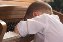Young Boy With Head On The Piano