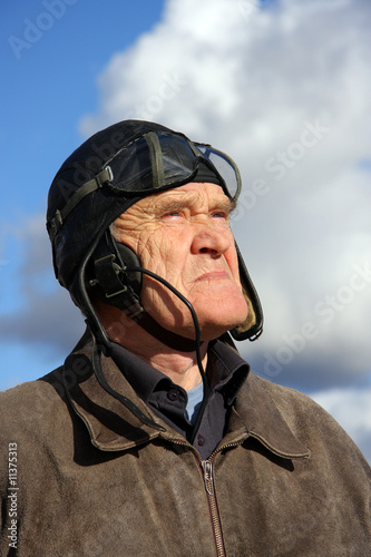 Fotomural old pilot in old uniform looking upstairs to the sky