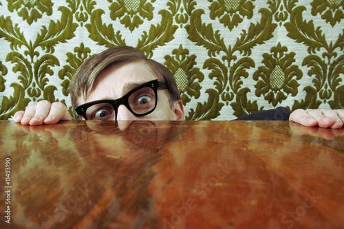 Scared nerd hiding behind a desk Canvas Print