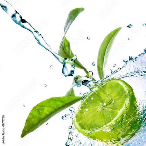 krople wody na wapno z zielonych liści na białym tle