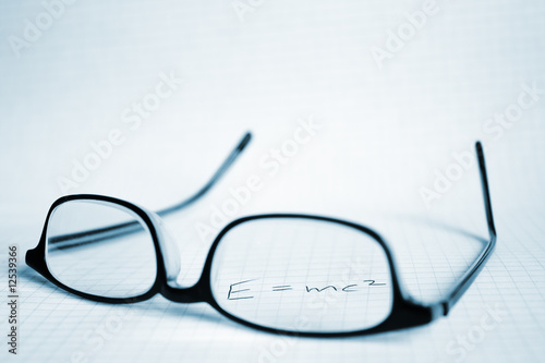 Photo  Glasses and paper with Albert Einstein's E=mc2