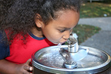 Girl Drinking From Water Fount...