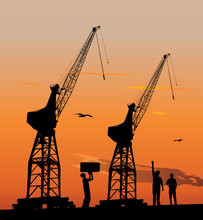 Silhouette Of Harbour Workers And Port Cranes At Sunset Sky