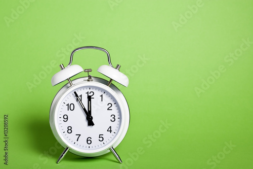 Photo  classic alarm clock on green background