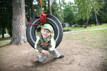 Young Boy Playing In Tire Swing