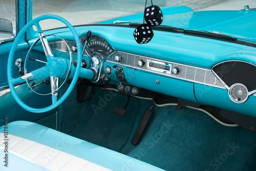Photo  Interior shot of a blue colored 1956 convertible with fuzzy dice