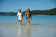 Two young women walking out of ocean