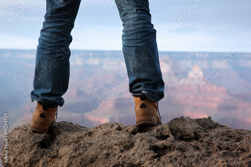 Tuinposter Canyon Male feet in hiking boots standing on edge of a cliff