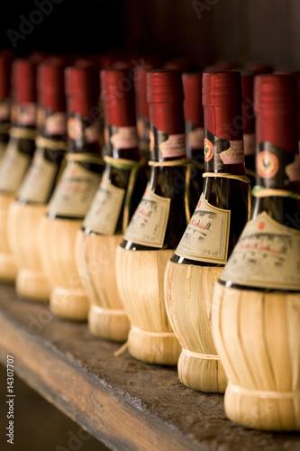 Fotografiet  Chianti wine bottles on a rack