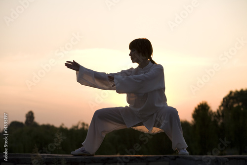 Fotografia  woman in white suit make's taiji chuan exercise