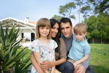 Familia Sentada Delante De Su Casa En Exterior