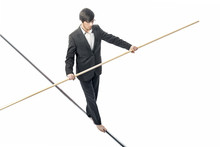 Businessman Walking A Tightrope - Isolated On White