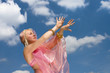 a woman in pink dress danccing and a blue sky