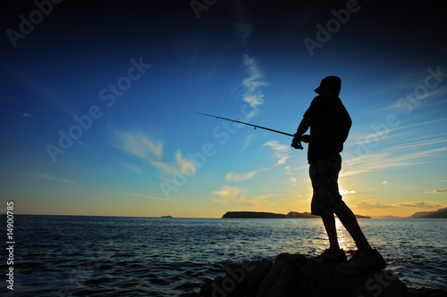 Fotografia Man fishing on sunset