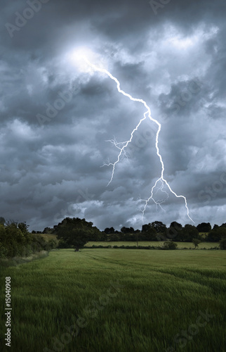Valokuvatapetti Lightening strike over field landscape
