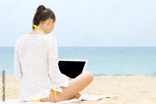 0085baa22259 Frau sitzt mit Laptop am Strand - Buy this stock photo and explore ...