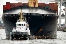 Tugboat Towing Freighter In Ha...