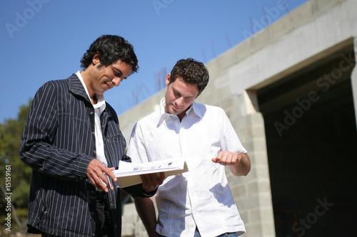Hommes discutants devant une maison en construction Canvas Print