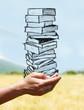 Leinwanddruck Bild - mains portant une pile de livres