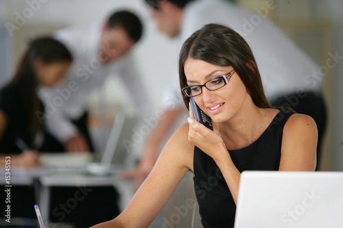 Vászonkép Femme souriante téléphonant en écrivant sur un document