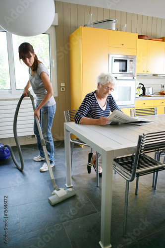 Photo Femme senior assise lisant le journal près d'une femme de ménage
