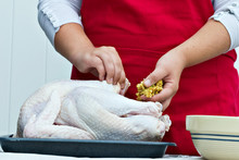 Woman's Hands Stuffing A Large Turkey For A Holiday Dinner.