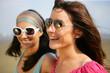 Deux femmes souriantes portant des lunettes de soleil