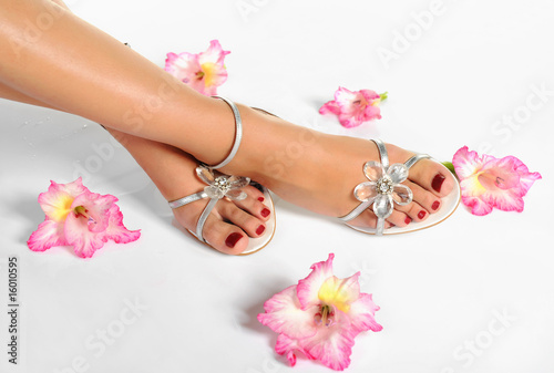 Foto op Aluminium Pedicure Beautiful woman legs with red manicure on the feet and flowers